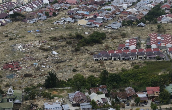 This Sunday, Oct. 7, 2018, aerial photo covers a part of the Petobo neighborhood wiped out by earthquake-triggered liquefaction in Palu, Central Sulawesi, Indonesia. All that remains of the village, located about 30 minutes from the city center, is a muddy wasteland where only the very tips of roofs remain above ground in some places. Satellite images show a heavily populated area stretching more than 100 hectares (250 acres) being devoured by what looks like a giant layer of chocolate milk. (AP Photo/Dita Alangkara)