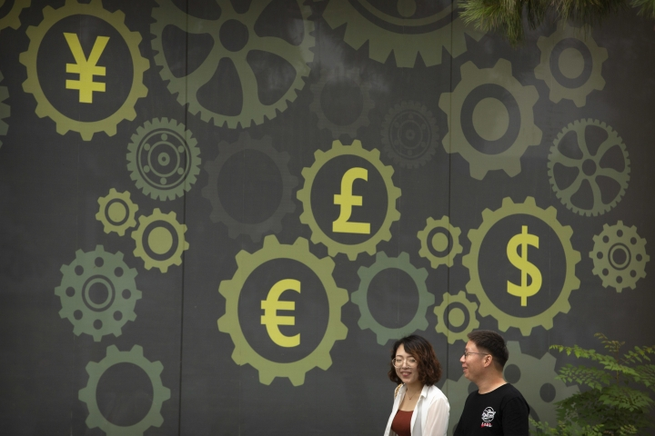 FILE - In this July 7, 2018 file photo, people walk past a mural on a bank showing symbols for American, Chinese and other world currencies in Beijing. The International Monetary Fund is downgrading its outlook for the world economy, citing rising interest rates and growing tensions over trade. The IMF said Monday, Oct. 8 that the global economy will grow 3.7 percent this year, the same as in 2017 but down from the 3.9 percent it was forecasting for 2018 in July. (AP Photo/Mark Schiefelbein, File)