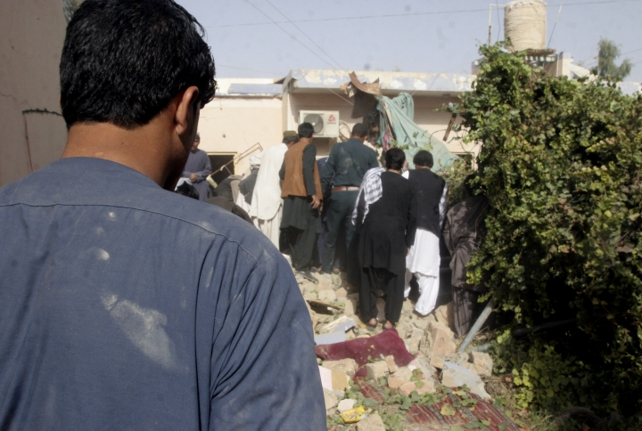 Afghans inspect the site of a suicide attack in Lashkar Gah, the capital of Helmand Province, Afghanistan, Tuesday, Oct. 9, 2018. A suicide bomber on Tuesday struck the home of a candidate in Afghanistan's parliamentary elections, that are to be held later this month, killing the candidate and seven other people, a provincial official said. (AP Photo/Abdul Khaliq)