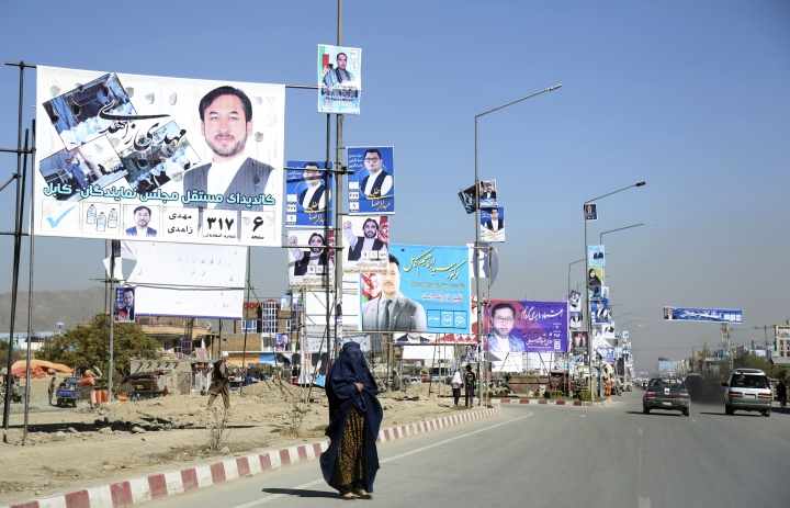 Campaign posters for parliamentary candidate are displayed over a street for the upcoming election, as a woman waits for transportation in Kabul, Afghanistan, Tuesday, Oct. 9, 2018. (AP Photo/Rahmat Gul)