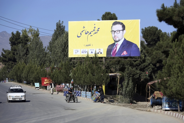 Campaign poster of the parliamentary candidate Mohammad Fahim Hashimi, is displayed over a street during the elections campaign for the upcoming election in Kabul, Afghanistan, Tuesday, Oct. 9, 2018. (AP Photo/Rahmat Gul)