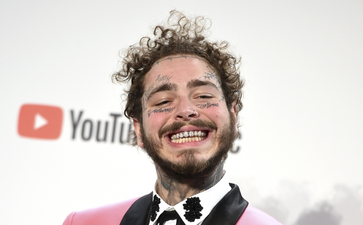 """Post Malone poses in the press room with the awards for favorite male pop/rock artist and favorite rap/hiphop album for """"Beerbongs & Bentleys"""" in the press room at the American Music Awards on Tuesday, Oct. 9, 2018, at the Microsoft Theater in Los Angeles. (Photo by Jordan Strauss/Invision/AP)"""