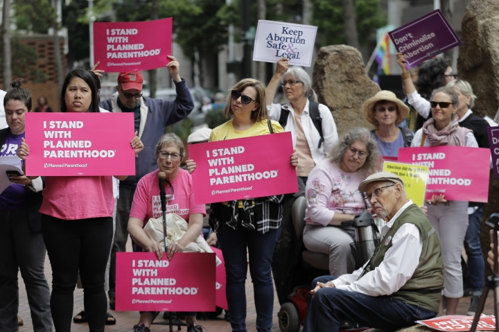 FILE - In this July 10, 2018 file photo, protesters hold signs supporting Planned Parenthood in Seattle, as they demonstrate against President Donald Trump and his choice of federal appeals Judge Brett Kavanaugh as his second nominee to the Supreme Court. On Wednesday, Oct. 10 Planned Parenthood unveiled a plan to protect access to abortion as widely as possible even if the Supreme Court moves to curtail women's right to undergo the procedure. (AP Photo/Ted S. Warren, File)