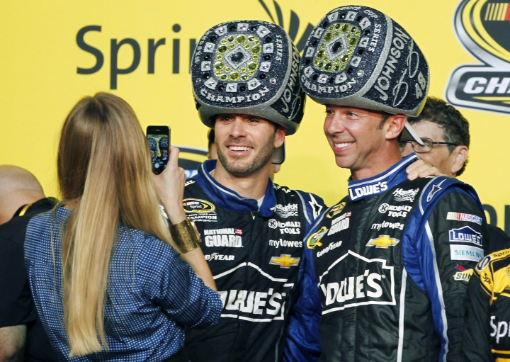 FILE - In this Nov. 17, 2013, file photo, Chandra Johnson takes photos of her husband, Jimmie Johnson, center, and his crew chief, Chad Knaus, after Jimmie won his sixth NASCAR Sprint Cup Series championship in Homestead, Fla. There will be no eighth NASCAR title for Johnson and Knaus. Hendrick Motorsports will split the driver and crew chief at the end of this season, the team announced Wednesday, Oct. 10, 2018. (AP Photo/Terry Renna, File)