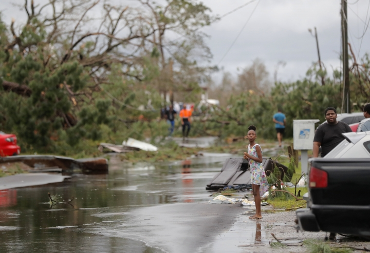 Tamiya Waldon looks out at the damage to her neighborhood in the aftermath of Hurricane Michael in Panama City, Fla., Wednesday, Oct. 10, 2018. (AP Photo/Gerald Herbert)