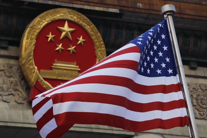 "FILE - In this Nov. 9, 2017, file photo, an American flag is flown next to the Chinese national emblem during a welcome ceremony for visiting U.S. China says accusations against an alleged spy of attempting to steal trade secrets from several American aviation and aerospace companies were ""made out of thin air."" (AP Photo/Andy Wong, File)"