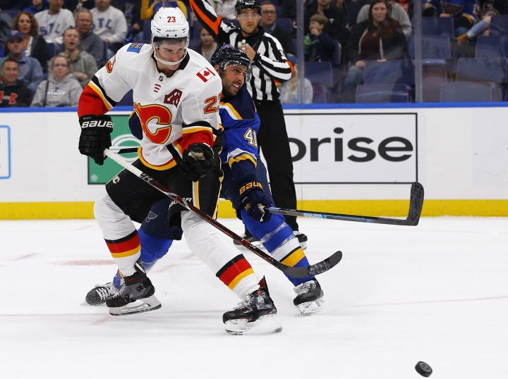 Calgary Flames' Sean Monahan, left, gets off a shot as he is pressured by St. Louis Blues' Robert Bortuzzo during the first period of an NHL hockey game Thursday, Oct. 11, 2018, in St. Louis. (AP Photo/Billy Hurst)