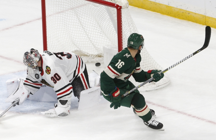 Minnesota Wild's Jason Zucker, right, watches his overtime goal against Chicago Blackhawks goalie Cam Ward in an NHL hockey game Thursday, Oct. 11, 2018, in St. Paul, Minn. The Wild won 4-3. It was Zucker's second goal of the game. (AP Photo/Jim Mone)