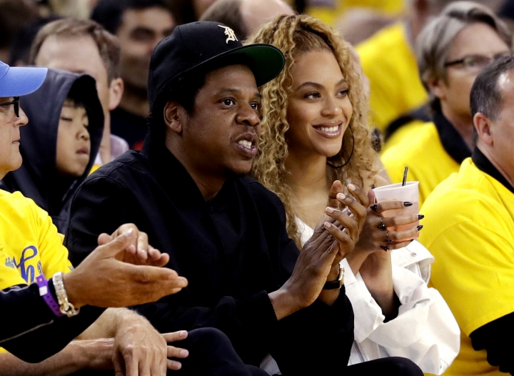 FILE - In this April 28, 2018, file photo, Jay-Z and Beyonce watch Game 1 of an NBA basketball second-round playoff series between the Golden State Warriors and the New Orleans Pelicans in Oakland, Calif. Beyonce paid homage to a high-profile music executive being honored at a charity event to raise money for cancer research. (AP Photo/Marcio Jose Sanchez, File)
