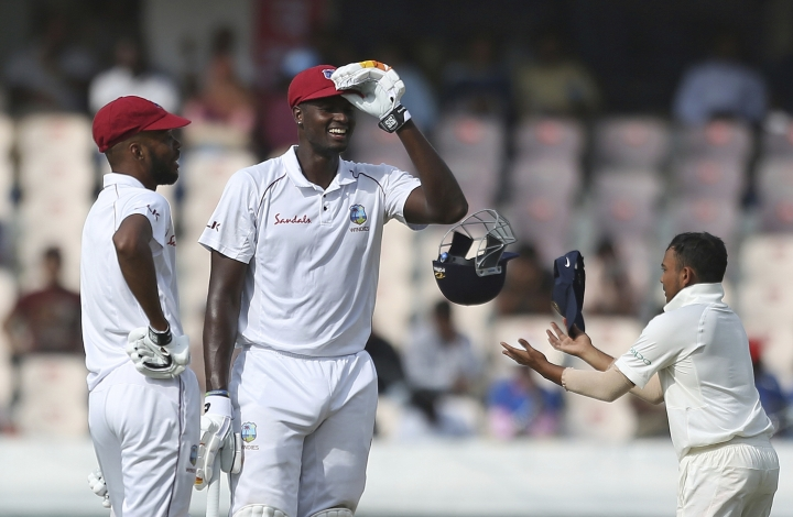 West Indies' cricket captain Jason Holder stands with his teammate Roston Chase during the first day of the second cricket test match between India and West Indies in Hyderabad, India, Friday, Oct. 12, 2018. (AP Photo/Mahesh Kumar A.)