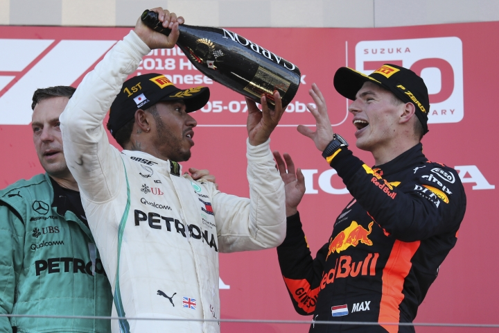 Race winner Mercedes driver Lewis Hamilton prepares to pour champagne on third placed Red Bull Racing driver Max Verstappen, left, as they celebrate on the podium at the Japanese Formula One Grand Prix at the Suzuka Circuit in Suzuka, central Japan, Sunday, Oct. 7, 2018. (AP Photo/Ng Han Guan)
