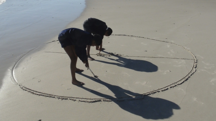 In this Tuesday, Aug. 21, 2018 photo, children from surrounding areas create calligraphy on a beach in Cape Town, South Africa. The Hangberg community outside South Africa's ruggedly beautiful Hout Bay is troubled by gang violence, drugs and poverty. One artist is trying to break the destructive cycle by teaching local children an unusual medium: beach calligraphy. (AP Photo/Neil Shaw)