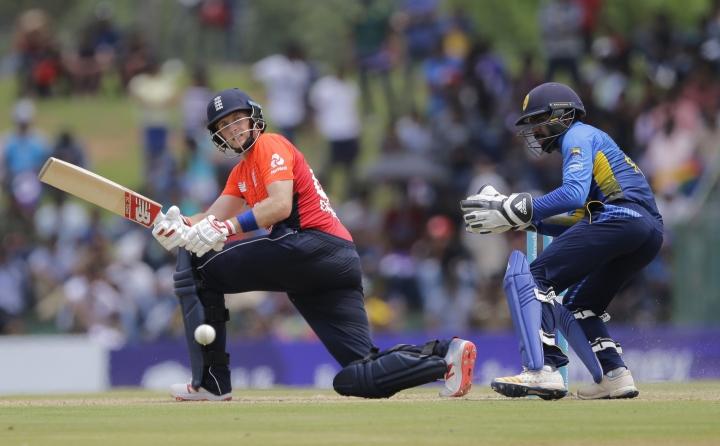 England's Joe Root plays a shot as Sri Lanka's wicketkeeper Niroshan Dickwella watches during their second one-day international cricket match in Dambulla, Sri Lanka, Saturday, Oct. 13, 2018. (AP Photo/Eranga Jayawardena)