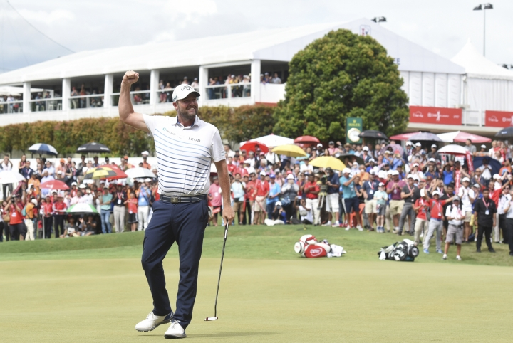 Marc Leishman of Australia celebrates after his putt on the eighteenth hole during final round of the CIMB Classic golf tournament at Tournament Players Club (TPC) in Kuala Lumpur, Malaysia, Sunday, Oct. 14, 2018. (AP Photo/Yam G-Jun)