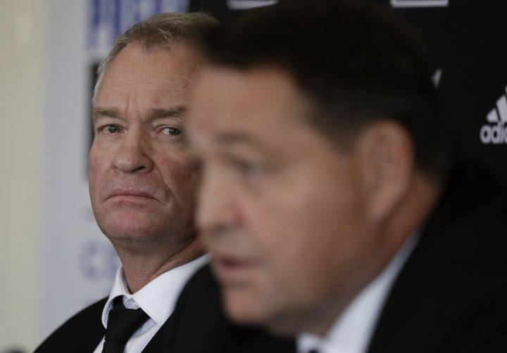 New Zealand All Blacks selector Grant Fox, left, watches as coach Steve Hansen answer's questions during a press conference at the Prebbleton Rugby Club on the outskirts of Christchurch, New Zealand, Monday, Oct. 15, 2018. The All Blacks have taken the unprecedented step of naming a player based in Japan among an enlarged 51-man squad for autumn test matches against Australia, Japan, England, Ireland and Italy. (AP Photo/Mark Baker)