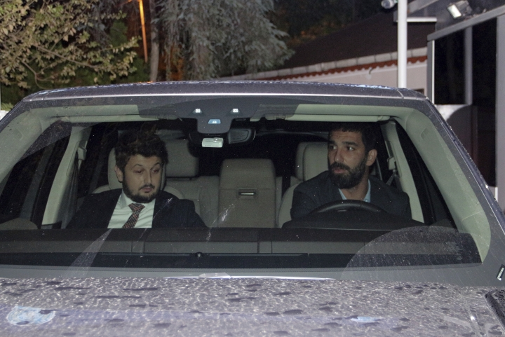 Barcelona's Turkish player Arda Turan, right, leaves a police station in Istanbul, Thursday, Oct. 11, 2018. Turan has given testimony to police following a nightclub brawl during which he reportedly broke the nose of a singer. The DHA news agency said Turan, who is on loan to Istanbul side Basaksehir, was called to a police station where he was questioned for three hours on Thursday. (IHA via AP)