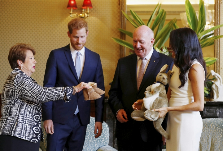Britain's Prince Harry and Meghan, Duchess of Sussex react as they receive gifts from by Australia's Governor General Sir Peter Cosgrove and his wife Lady Cosgrove at Admiralty House in Sydney, Australia, Tuesday, Oct. 16, 2018. Prince Harry and his wife Meghan are on a 16-day tour of Australia and the South Pacific.(Phil Noble/Pool via AP)