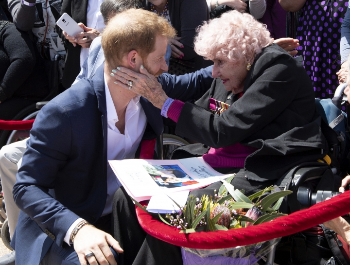 Britain's Prince Harry is embraced by 97-year-old Dafney Dunne during a walk about outside the Opera House in Sydney, Australia, Tuesday, Oct. 16, 2018. Prince Harry and his wife Meghan are on a 16-day tour of Australia and the South Pacific (Paul Edwards/Pool via AP)