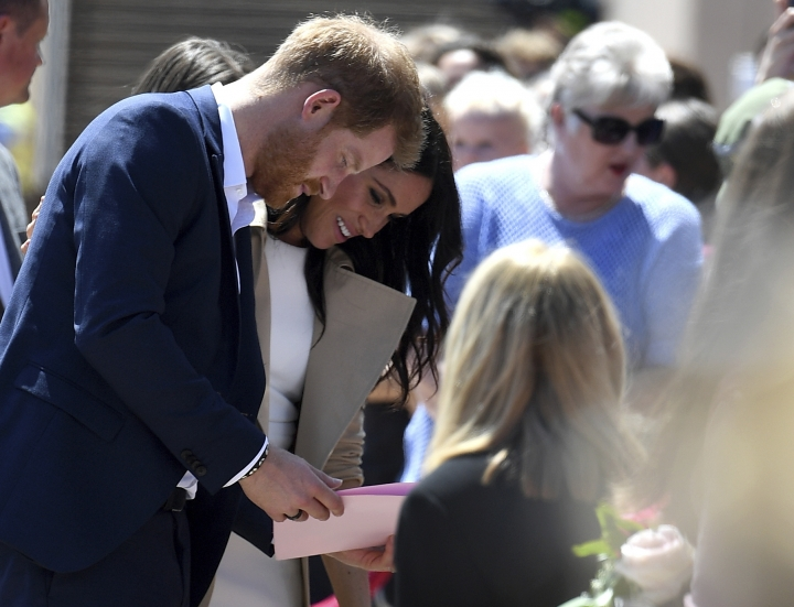 Britain's Prince Harry and Meghan, Duchess of Sussex meet members of the public outside the Opera House in Sydney, Australia, Tuesday, Oct. 16, 2018. Prince Harry and his wife Meghan are on a 16-day tour of Australia and the South Pacific. (Dan Himbrechts/Pool via AP)