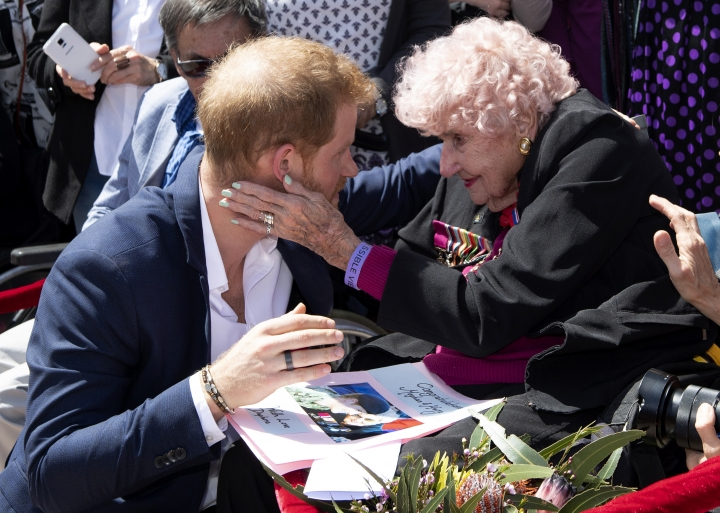 Britain's Prince Harry is embraced by 98-year-old Daphne Dunne during a walkabout outside the Opera House in Sydney, Australia, Tuesday, Oct. 16, 2018. (Paul Edwards/Pool Photo via AP)