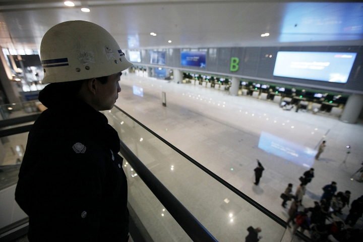 FILE - In this Jan. 21, 2010, file photo, a security officer stands guard at the new Terminal 2 building under construction at Shanghai Hongqiao International Airport in Shanghai. It's now possible to check in automatically at Shanghai's Hongqiao airport using facial recognition technology, part of an ambitious rollout of facial recognition systems in China that has raised privacy concerns as Beijing pushes to become a global leader in the field. The airport unveiled self-service kiosks for flight and baggage check-in, security clearance and boarding powered by facial recognition technology, according to the Civil Aviation Administration of China. (AP Photo/Eugene Hoshiko, File)