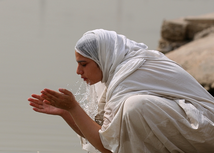 In this Sunday, Oct. 14, 2018 photo, a follower of the obscure and ancient Mandaean faith performs rituals along a strip of embankment on the Tigris River reserved for them, in Baghdad, Iraq. Every Sunday worshippers bathe themselves in the waters to purify their souls. But unlike in ancient times, the storied river that runs through Baghdad is fouled by the smells of untreated sewage and dead carp, which float by in the fast-moving current. (AP Photo/Hadi Mizban)
