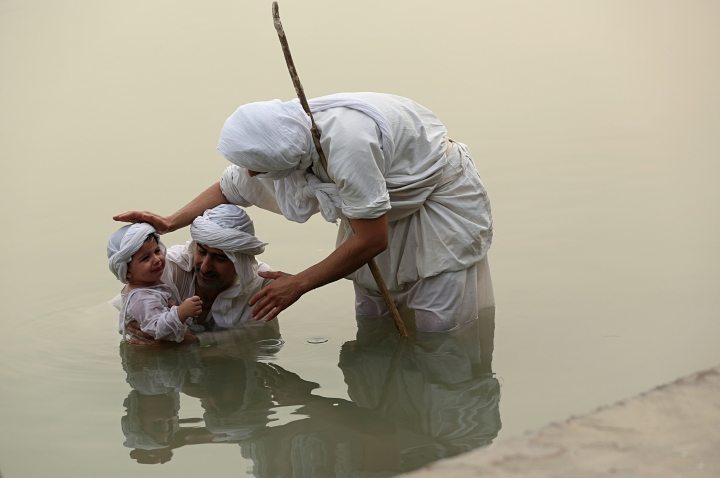 In this Sunday, Oct. 14, 2018 photo, a follower of the obscure and ancient Mandaean faith baptizes a child along a strip of embankment on the Tigris River reserved for them, in Baghdad, Iraq. Iraq's soaring water pollution is threatening the religious rites of its tight-knit Mandaean community, already devastated by 15 years of war that has also affected the country's other minority Abrahamic sects. (AP Photo/Hadi Mizban)