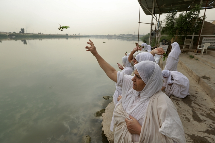In this Sunday, Oct. 14, 2018 photo, followers of the obscure and ancient Mandaean faith throw parsley from an embankment on the Tigris River as part of their traditional rituals, in Baghdad, Iraq. Until 2003, nearly all the world's Mandaeans lived in Iraq, but the cycles of conflict since the U.S. invasion have driven minorities out of the country for security reasons and economic opportunity. (AP Photo/Hadi Mizban)
