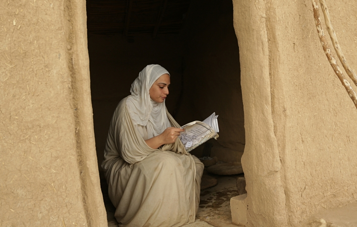 In this Sunday, Oct. 14, 2018 photo, a follower of the obscure and ancient Mandaean faith reads from a religious book in the doorway of a mud building along a strip of embankment on the Tigris River reserved for them, in Baghdad, Iraq. Mandaeism follows the teachings of John the Baptist, a saint in both the Christian and Islamic traditions, and its rites revolve around water. (AP Photo/Hadi Mizban)