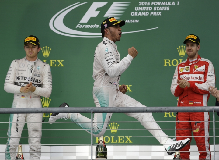 FILE - In this Sunday, Oct. 25, 2015, file photo, Mercedes driver Lewis Hamilton celebrates, flanked by teammate, Germany's Nico Rosberg, left, and Ferrari driver Sebastian Vettel of Germany, after winning the Formula One world championship with his victory at the U.S. Grand Prix race at the Circuit of the Americas, in Austin, Texas. Once again, the race figures prominently in the season title chase. Lewis Hamilton can close out Sebastian Vettel to clinch his fifth season championship on the track where he has won five times. (AP Photo/Darron Cummings, File)