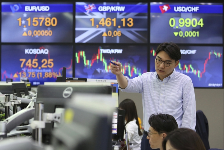 A currency trader gestures at the foreign exchange dealing room of the KEB Hana Bank headquarters in Seoul, South Korea, Wednesday, Oct. 17, 2018. Asian markets rose on Wednesday, bolstered by robust U.S. corporate earnings and encouraging. (AP Photo/Ahn Young-joon)