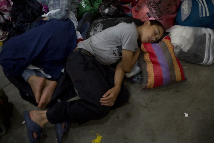 Honduran migrants rest at an improvised shelter in Chiquimula, Guatemala, Tuesday, Oct. 16, 2018. U.S. President Donald Trump threatened on Tuesday to cut aid to Honduras if it doesn't stop the impromptu caravan of migrants, but it remains unclear if governments in the region can summon the political will to physically halt the determined border-crossers. (AP Photo/Moises Castillo)
