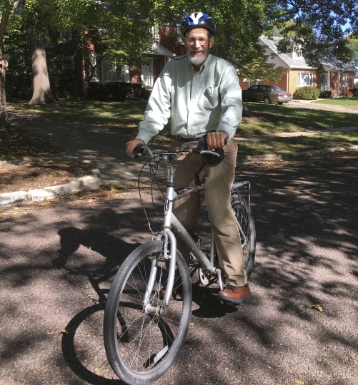 In this Oct. 17, 2018 photo provided by Marjorie Sable, George Smith, professor emeritus at the University of Missouri who won the 2018 Nobel Prize for chemistry. rides his bike on a biking/walking trail in Columbia, Mo. The university is honoring its Nobel Prize-winning scientist with an unusual accolade: a dedicated bicycle rack slot. It will be a standard bike rack, the same as those used by other bicyclists on campus. But the university plans to post a sign letting everyone know that this particular space belongs to a Nobel laureate. (Marjorie Sable photo via AP)