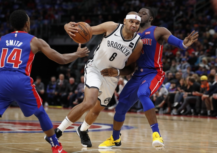 Brooklyn Nets forward Jared Dudley (6) drives between Detroit Pistons guards Ish Smith (14) and Reggie Jackson (1) during the first half of an NBA basketball game, Wednesday, Oct. 17, 2018, in Detroit. (AP Photo/Carlos Osorio)