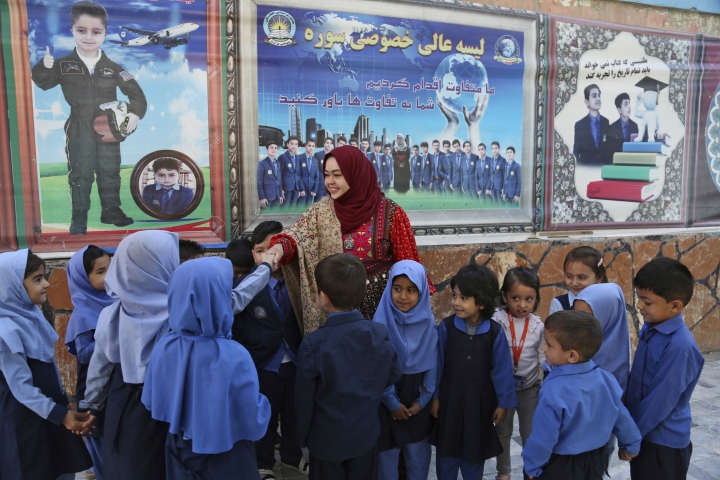 In this Sunday, Oct. 14, 2018 photo, Hameeda Danesh, a candidate for Parliament, hoping to represent the deeply conservative district of Jalrez in central Wardak province, visits a school, in Kabul, Afghanistan. In Saturday's election 417, or roughly 16 percent, of the 2,565 candidates competing for seats in the 249-member chamber are women. Yet in rural Afghanistan, especially in the country's ethnic Pashtun areas where the Taliban dominate, many women are not even registered to vote. (AP Photo/Rahmat Gul)