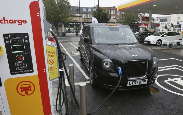 FILE - In this file image dated Wednesday Oct. 18, 2017, 2017, a new TX Cab London taxi is plugged into a charging station in London. London's black cabs will be seen on the streets of Paris next year as the London Electric Vehicle Company has announced Thursday Oct. 18, 2018, that they will begin selling its wares in the City of Light. (AP Photo/Tim Ireland, FILE)