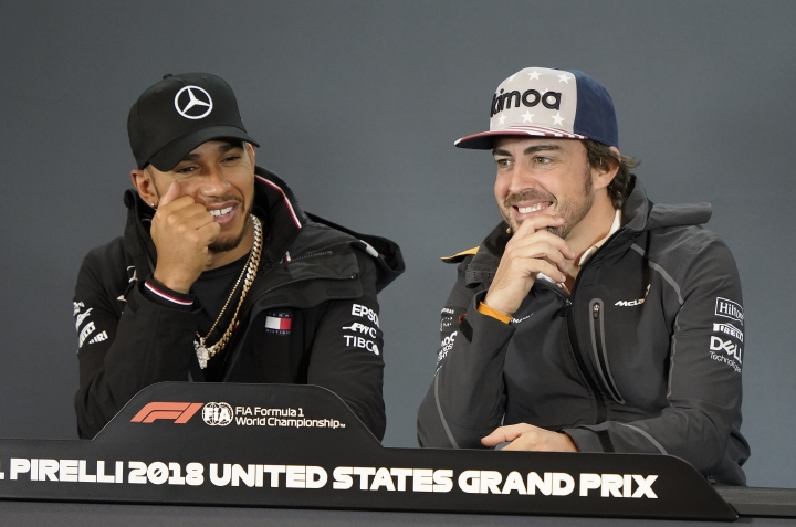 Mercedes driver Lewis Hamilton, left, of Britain, talks wot McLaren driver Fernando Alonso, of Spain, during a news conference for the Formula One U.S. Grand Prix auto race at the Circuit of the Americas, Thursday, Oct. 18, 2018, in Austin, Texas. (AP Photo/Darren Abate)