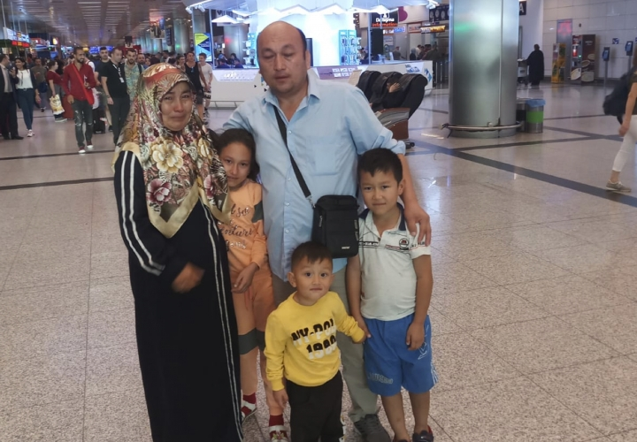 In this photo taken Sept. 29, 2018, and released on Oct. 18, 2018, by Omar Bekali, Bekali, center, poses with his family in an airport after being reunited with his wife and son on September 19, 2018, in Istanbul, Turkey. Bekali, an outspoken former detainee of China's internment camps for Muslims, says his application for a visa to visit the United States was rejected despite an invitation to speak at Congress about his ordeal. (Omir Bekali via AP)