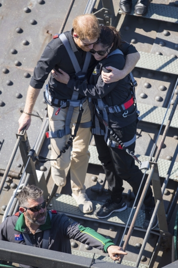 Britain's Prince Harry, left, hugs a fellow climber during a visit to the Sydney Harbour Bridge with Prime Minister of Australia Scott Morrison and Invictus Games competitors in Sydney, Friday, Oct. 19, 2018. Prince Harry and his wife Meghan are on day four of their 16-day tour of Australia and the South Pacific.(Dominic Lipinski/Pool Photo via AP)