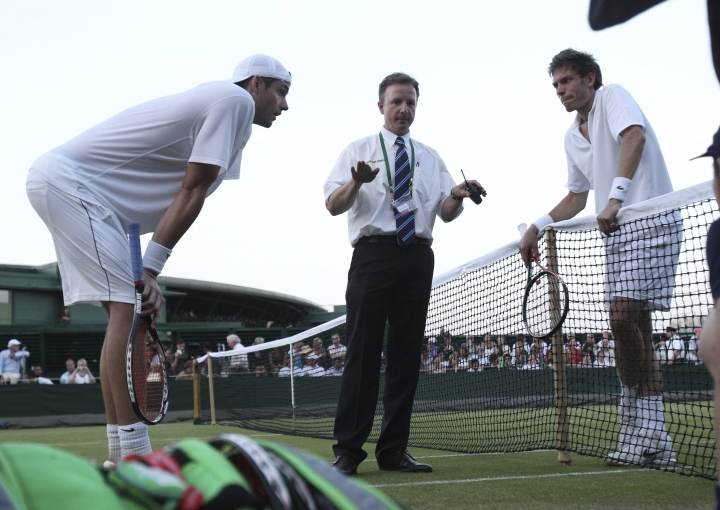 FILE - In this June 23, 2010 file photo, referee Soeren Friemel, calls off the record-breaking men's singles match between John Isner of the U.S., left, and Nicolas Mahut of France, because of bad light, at the All England Lawn Tennis Championships at Wimbledon. The All England Club said Friday Oct. 19, 2018, it will introduce fifth-set tiebreakers at Wimbledon next year when a match reaches 12-12. (AP Photo/Alastair Grant, File)