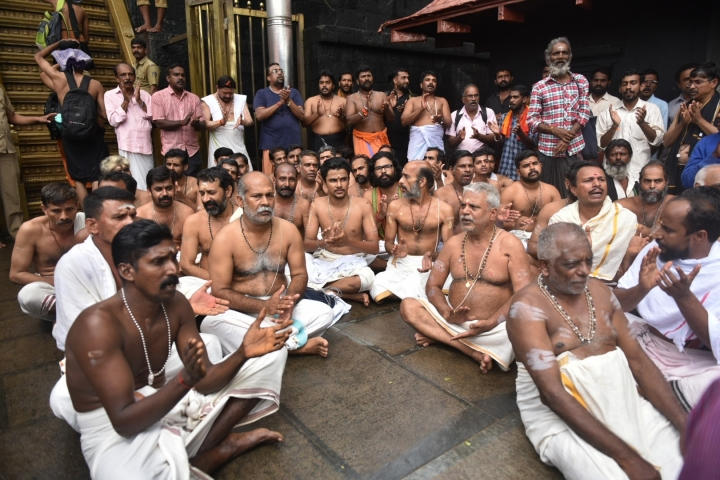 Hindu priests and temple staff sit on a protest against a ruling from India's top court to let women of menstruating age entering Sabarimala temple, one of the world's largest Hindu pilgrimage sites, in the southern Indian state of Kerala, Friday, Oct. 19, 2018. The country's Supreme Court had on Sept. 28, lifted the temple's ban on women of menstruating age, holding that equality is supreme irrespective of age and gender. Two young women, a journalist and an activist, were forced to turn back after they had reached the temple precincts under a heavy police escort. (AP Photo)