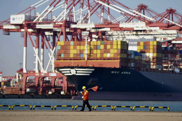 In this Friday, Oct. 12, 2018, photo, a worker walks by the container ship docked at a port in Qingdao in east China's Shandong province. China's economic growth slowed further in the latest quarter, adding to challenges for communist leaders who are fighting a mounting tariff battle with Washington. (Chinatopix via AP)