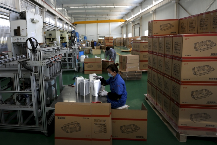 In this Thursday, Oct. 11, 2018, photo, workers pack disposable aluminum foil food containers for export at a factory in Suixi county in central China's Anhui province. China's economic growth slowed further in the latest quarter, adding to challenges for communist leaders who are fighting a mounting tariff battle with Washington. (Chinatopix via AP)