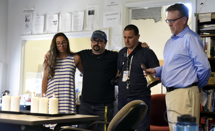 FILE - In thie July 5, 2018 file photo, Rick Hutzell, right, the editor for Capital Gazette, is joined by staff members, from left, reporter Selene San Felice, and photojournalists Paul W. Gillespie and Joshua McKerrow, as he rings a bell during a moment of silence at 2:33 p.m., Thursday, July 5, 2018, in Annapolis, Md., Hutzell has won the Benjamin C. Bradlee Editor of the Year Award. The National Press Foundation announced the award Friday, Oct. 19 to the editor of Capital Gazette Communications in Annapolis, Md. (Brian Krista/The Baltimore Sun via AP)