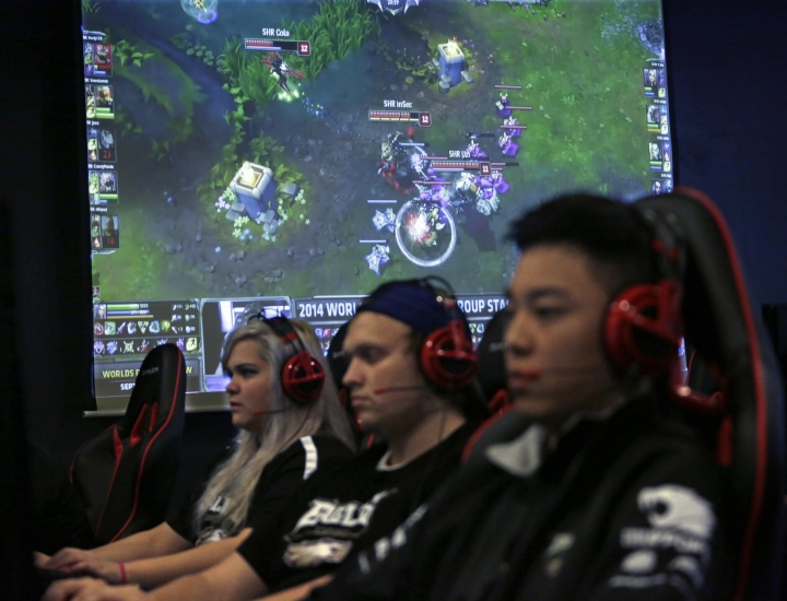 "FILE - In this Sept. 23, 2014, file photo, Robert Morris University Illinois freshmen, from left, Sondra Burrows, Brian Rodonis and Alex Chapman practice playing the video game ""League of Legends"" with their collegiate teammates at their on-campus training facility in Chicago. Die-hard esports fans are gathering by the thousands in South Korea this month to watch the world's top League of Legends players show off their skill and expertise. In the United States, the game's publisher is hoping to draw a more casual crowd by starting with an important question: What is League of Legends? (AP Photo/M. Spencer Green, File)"