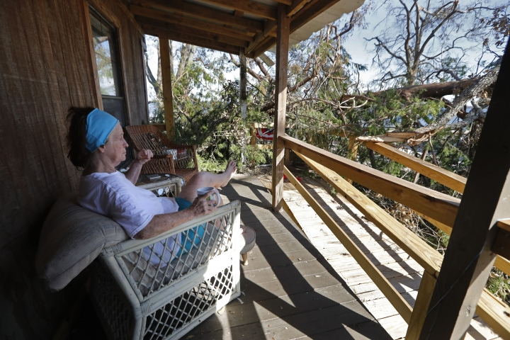 Joyce Walker sits on her porch in front fallen trees outside her home in the aftermath of Hurricane Michael in Panama City, Fla., Wednesday, Oct. 17, 2018. (AP Photo/Gerald Herbert)