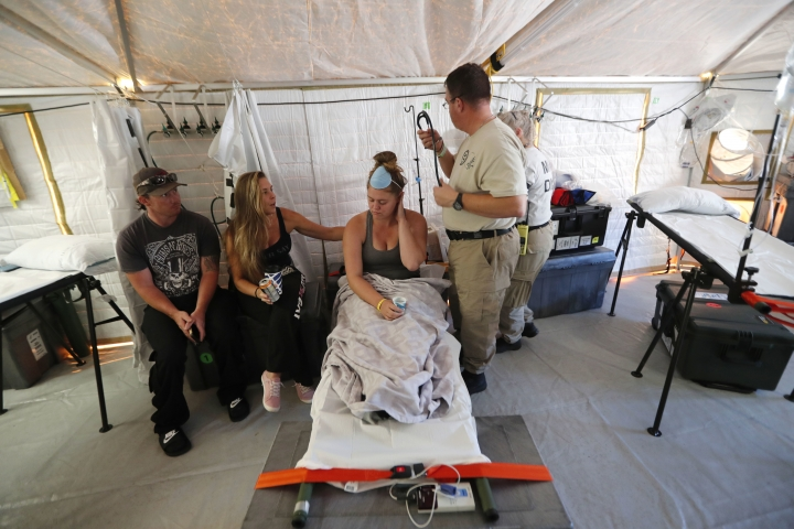 Aleeah Racette receives medical treatment inside the Florida 5 Disaster Medical Assistance Team tent, outside the Bay Medical Sacred Heart hospital, in the aftermath of Hurricane Michael in Mexico Beach, Fla., Thursday, Oct. 18, 2018. At left is her mother, Amy Cross, and Amy's fiance, Corey Shuman. (AP Photo/Gerald Herbert)