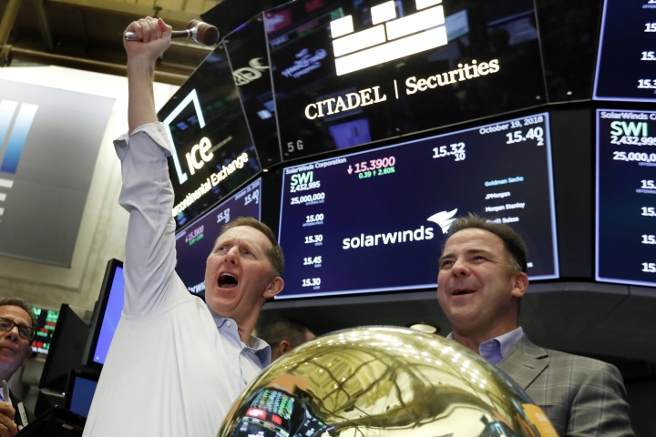 Solarwinds Chairman & CEO Kevin Thompson, left, and CFO Bart Kalsu celebrate as their company's IPO begins trading on the floor of the New York Stock Exchange, Friday, Oct. 19, 2018. (AP Photo/Richard Drew)