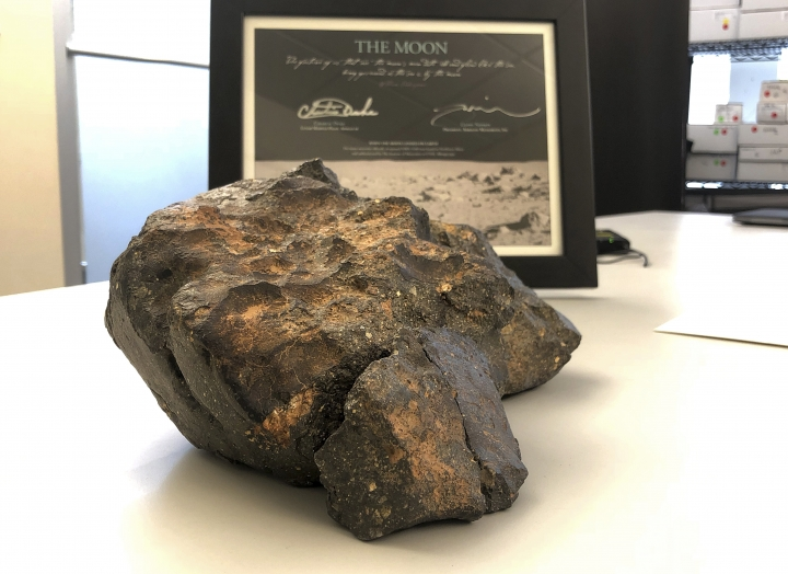 FILE - In this Oct. 10, 2018 file photo, a 12-pound (5.5 kilogram) lunar meteorite discovered in Northwest Africa in 2017 rests on a table, in Amherst, N.H. On Friday, Oct. 19, 2018, Boston-based RR Auction announced that the $612,500 winning bid for the meteorite, composed of six fragments that fit together like a puzzle, came from a representative working with the Tam Chuc Pagoda complex in Ha Nam Province, Vietnam. (AP Photo/Rodrique Ngowi)