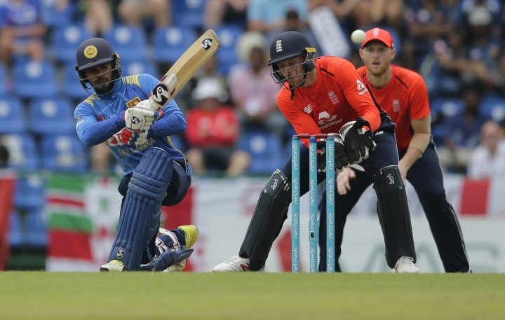 Sri Lanka's Dhananjaya de Silva plays a shot as England's wicketkeeper Jos Buttler watches during their fourth one-day international cricket match in Pallekele, Sri Lanka, Saturday, Oct. 20, 2018. (AP Photo/Eranga Jayawardena)